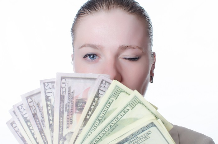 A woman winks as she holds out a fan of cash.