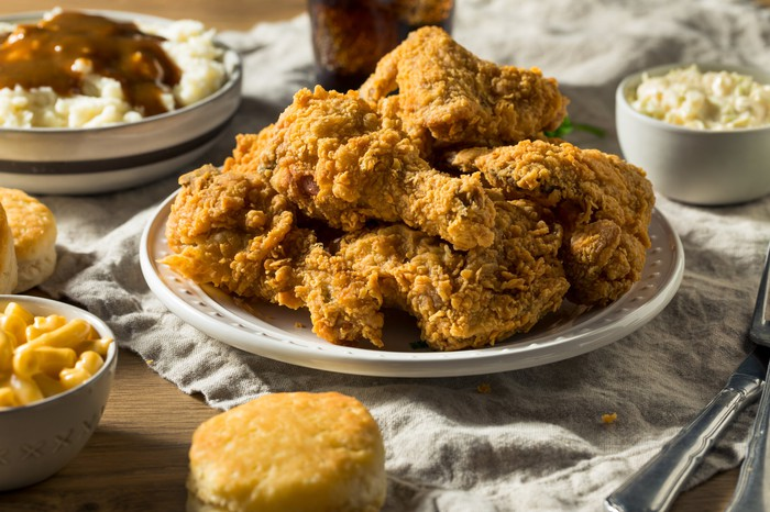 A plate of fried chicken surrounded by biscuits, mashed potatoes, and mac and cheese.