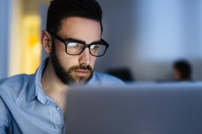 Man with serious expression looking at laptop screen