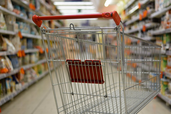 An empty shopping cart in a grocery store aisle.