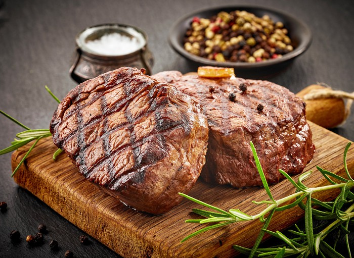 Two grilled steaks sit on a wooden serving board, flanked by condiments and sides.