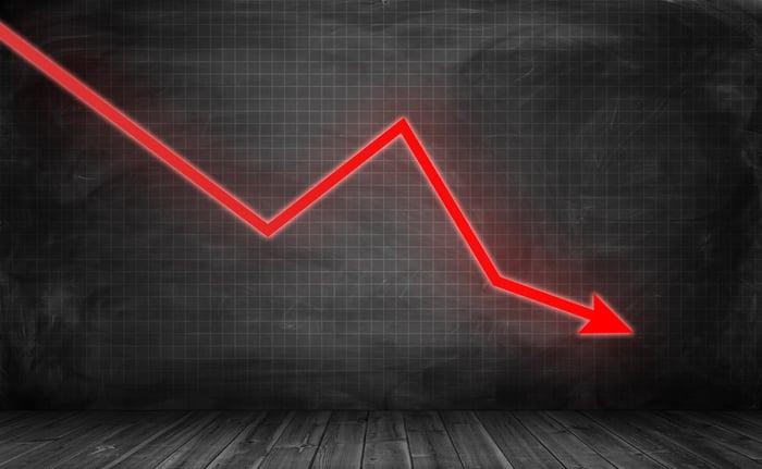 A downward trending red arrow set against a black background.
