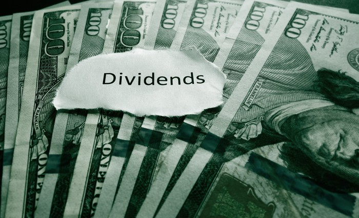 A piece of paper with the word dividends written on it on top of nundred dollar bills.