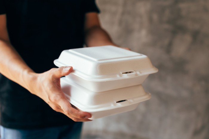 A man in a black t-shirt carries two Styrofoam takeout boxes.