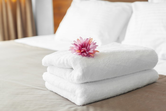 Fresh towels on a hotel bed.