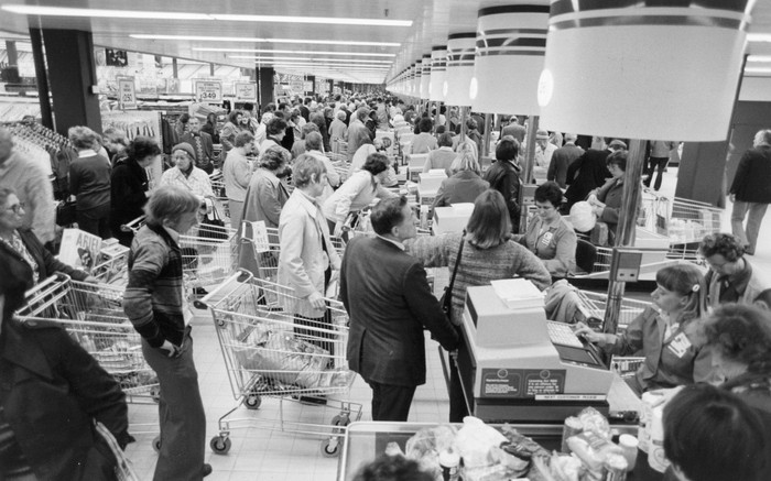 A black and white image of crowded grocery store checkout lines