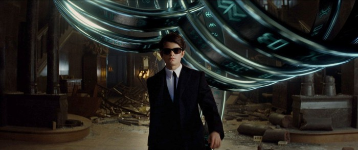 "A screenshot from Disney's ""Artemis Fowl"" showing a young kid wearing a black suit and sunglasses."