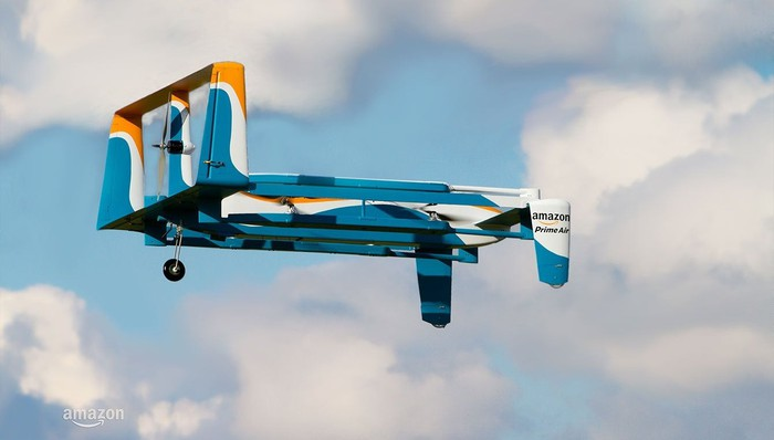 Amazon Prime Air drone in the air with clouds and blue sky behind it.