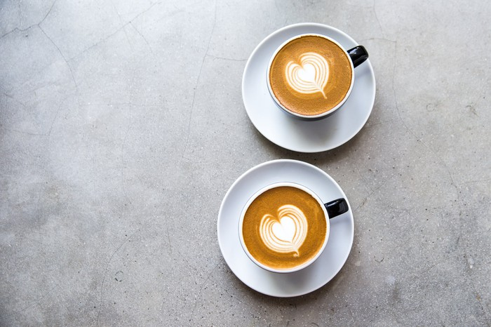 Two cups of coffee with milk hearts.