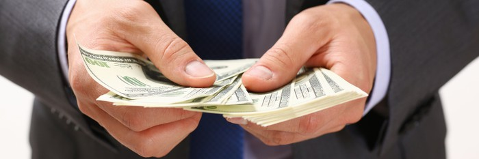 Banker counting out cash to loan