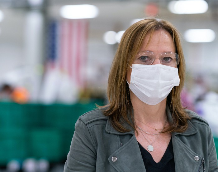 Barra is shown wearing a mask and safety glasses, standing on a factory floor.