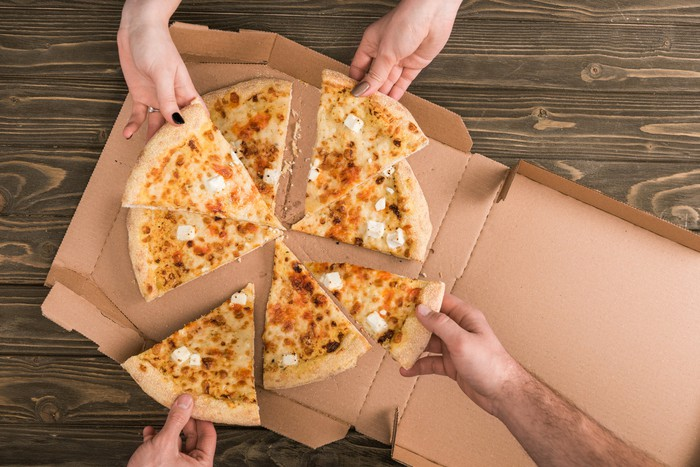 Four people sharing a pizza out of a box.