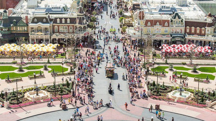 A crowd of people walking in a Disney theme park.