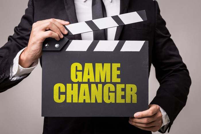 Man holding a clapperboard with Game Changer printed on it