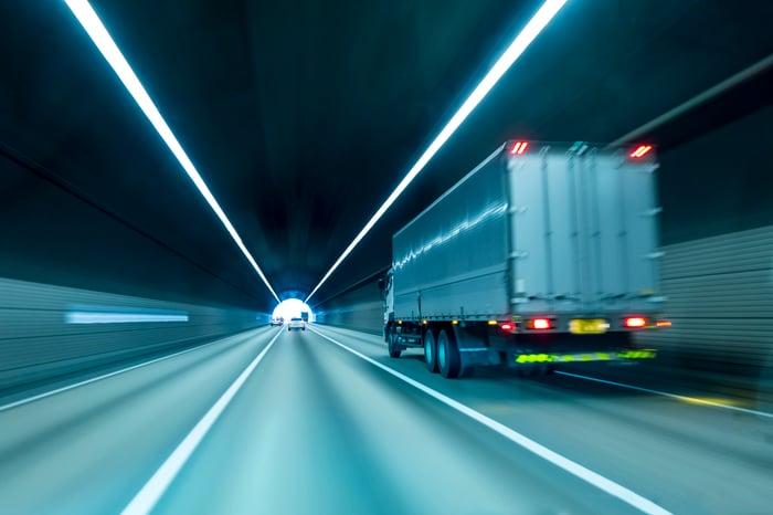 Tractor trailer speeding through a tunnel.
