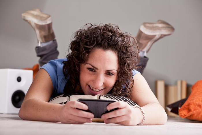 A young woman laying on the floor using a smartphone.