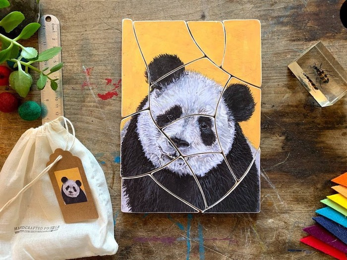 A 12-piece panda puzzle against a wood background