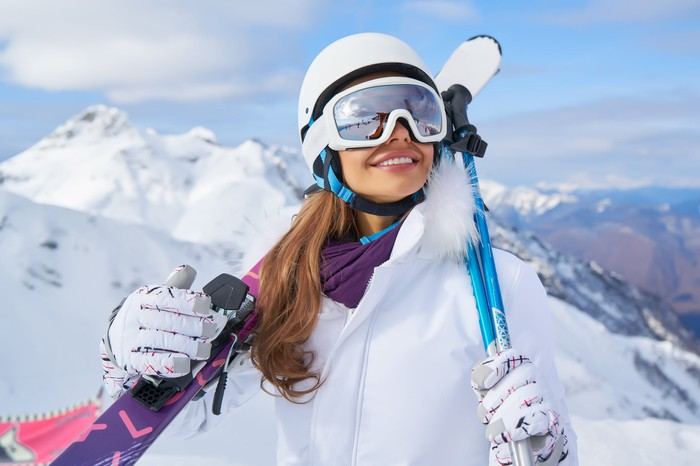 A woman in ski gear smiling with a mountain in the background.