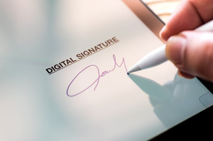 Person's hand signing a tablet with a digital pen,