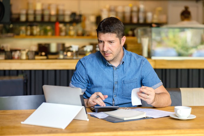 Man holding receipt and typing on calculator with ledger, mug, and tablet on table in front of him