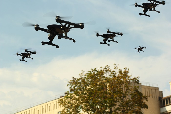 Aerial drones fly over a building.