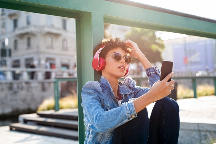 A young person leaning against a post outdoors wearing red headphones while looking at a mobile phone.