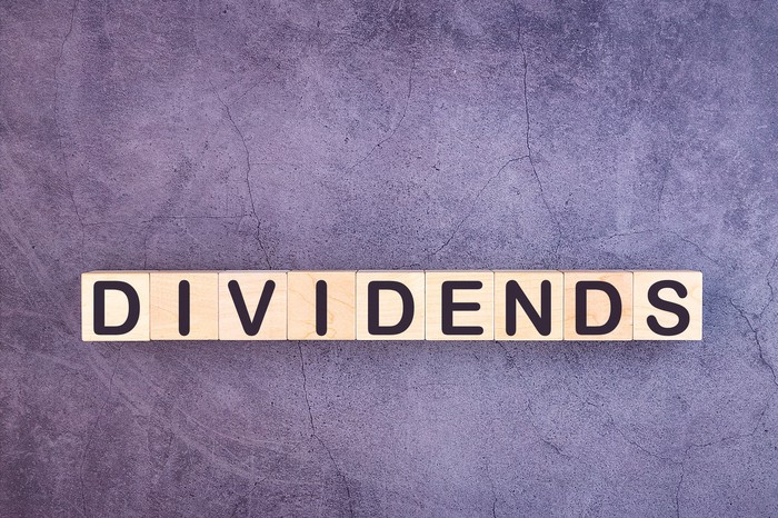 "The word ""dividends"" spelled out on wooden blocks against a gray background."