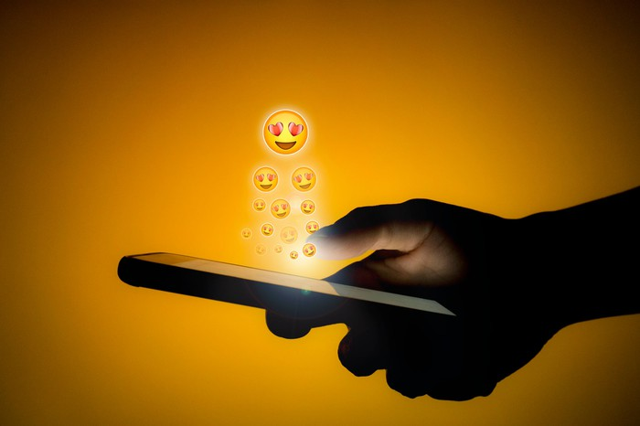Emojis with heart-shaped eyes rise out a smartphone.