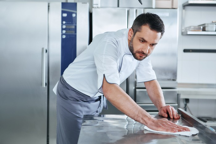 A chef cleaning a kitchen counter.