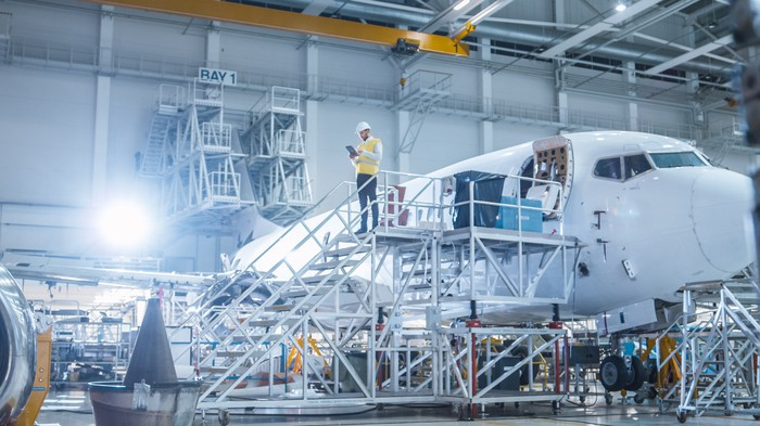 Worker on platform in aircraft manufacturing plant. Behind the worker is a plane.