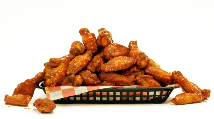 A large pile of chicken wings in a basket.