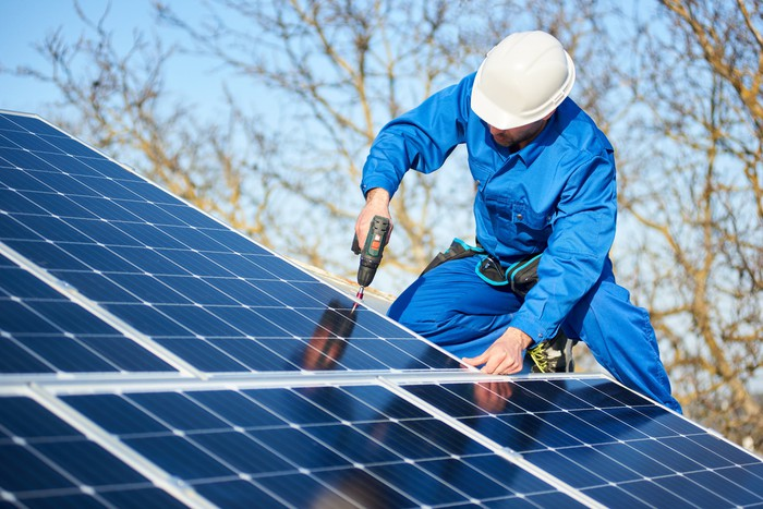 Worker in blue jumpsuit and white hardhat installs solar panels on a rooftop