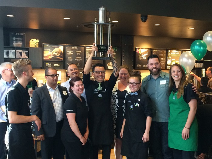 A group of starbucks baristas, with one holding a large trophy.
