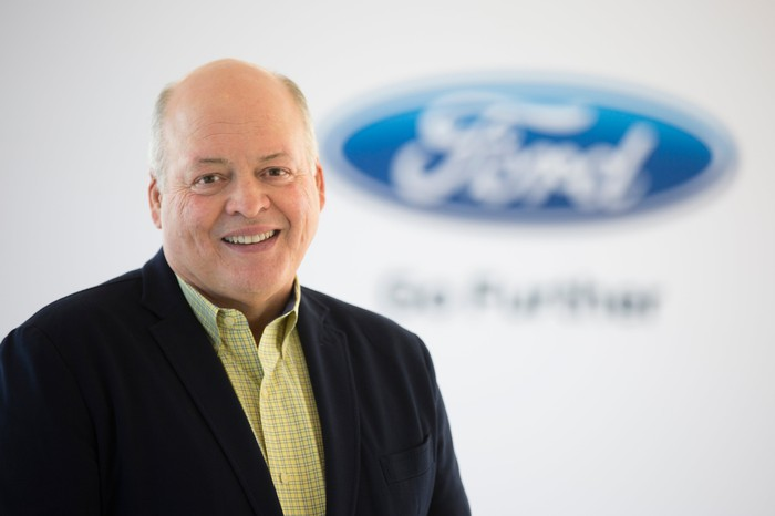 Ford CEO Jim Hackett is shown standing in front of a white backdrop with a blue Ford logo.