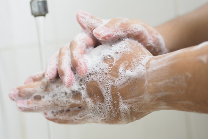 closeup on hands washing under a sink.