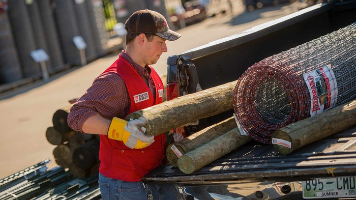 A Tractor Supply worker loading a truck.