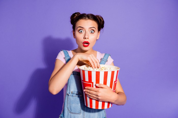 A young woman with a surprised expression on her face dips into a very large bucket of popcorn.