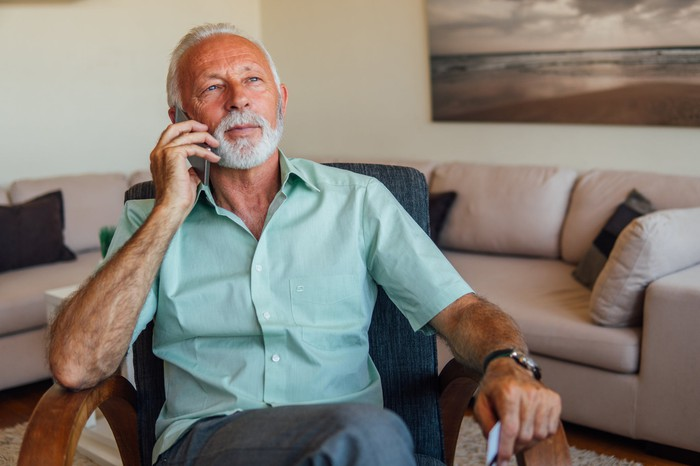 Older man seated in armchair talking on phone