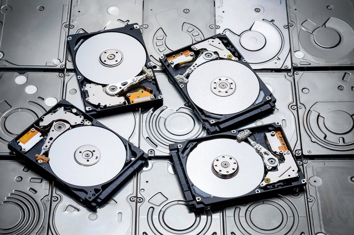 Four open and overturned HDDs on top of other HDDs.