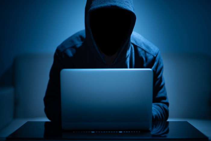 A shadowed man in a hoodie sits in front of a laptop.