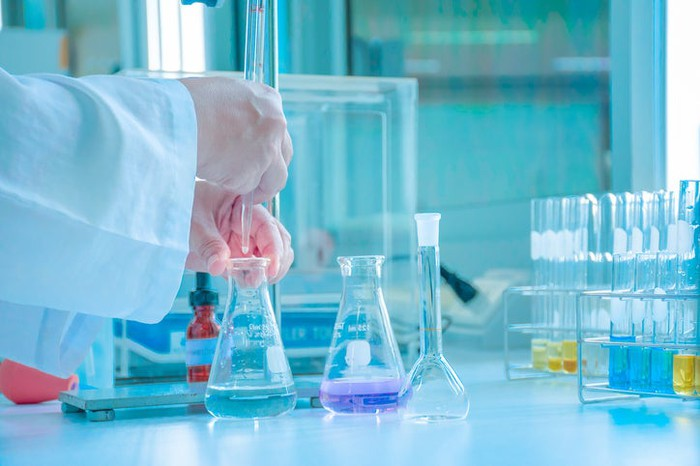Hands of someone wearing a white lab coat mixing liquids in glass beakers on a white table.
