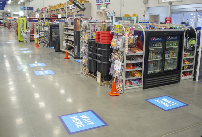 The interior of a Lowe's with blue floor signs for social distancing guides.