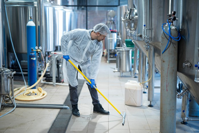 A worker disinfecting an industrial facility by hand.