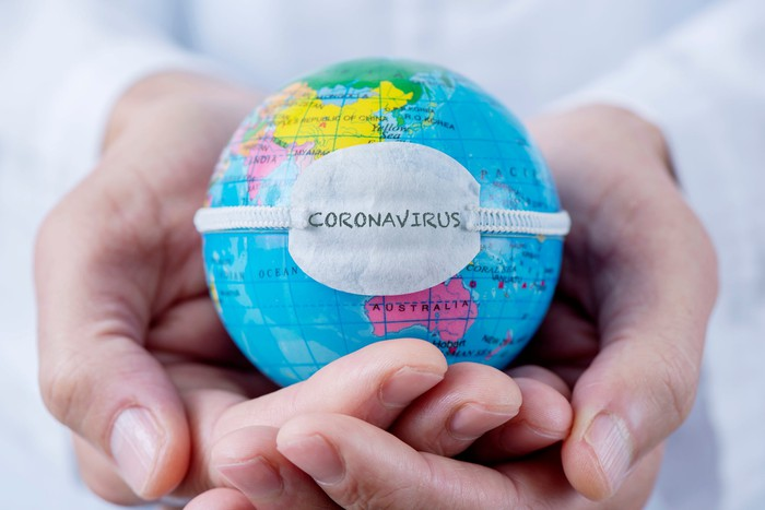 A small Earth globe, wrapped in a tiny face mask with the word Coronavirus written on it, held by a person in a white lab coat.