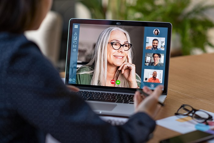 A person having a video conference with a computer screen showing others on the virtual video call.