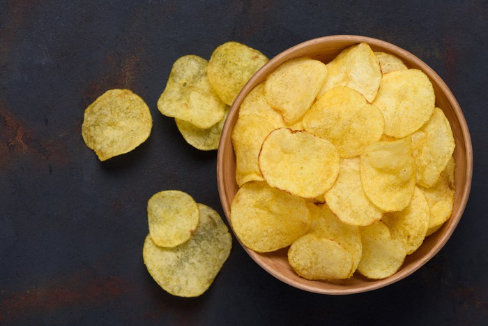 A bowl of chips on a wooden table with a few chips scattered around it.