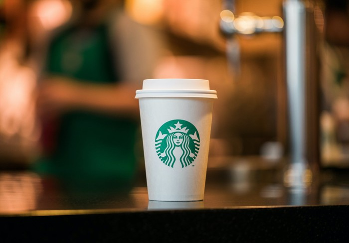 A Starbucks coffee cup, with the company's green logo visible.