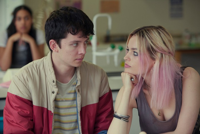 In a scene from Netflix's Sex Education, young couple looks intently into each other's eyes.
