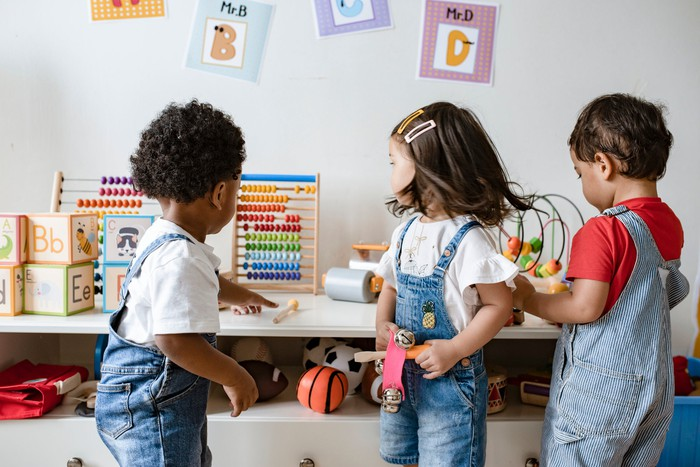 Three children playing with toys in a playroom.