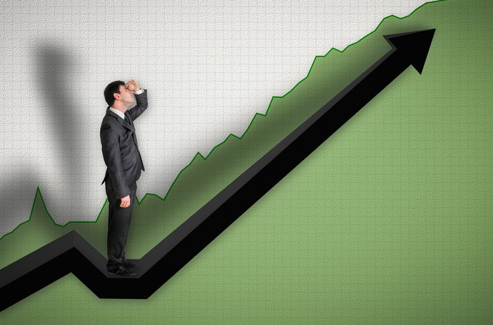 Person in a suit looking up at an upward sloping chart.